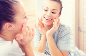 Woman looking in mirror at smooth skin on her face