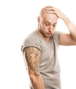 Man looking at tattoo on upper arm