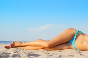Woman with smooth legs laying on sand at beach